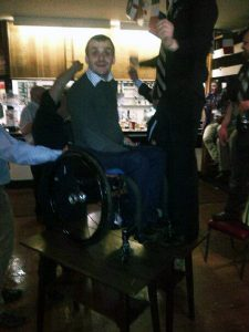Andy Barrow in his wheelchair on a table